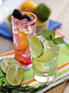 Two refreshing summer cocktails with lime, mint, cranberry on a table